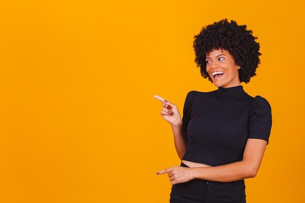 Horizontaal schot van vrij jonge vrolijke afro-amerikaanse vrouwelijke punten met wijsvinger weg, geeft kopie ruimte aan