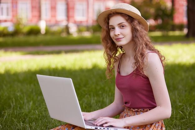 Horizontaal schot van vrij jonge vrouwenzitting op groen gras in park met draagbare computer op benen tijdens de zomerdag, gebruikend draadloos internet voor online werkend, vrouwelijk dragend t-shirt en strohoed.