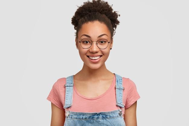 Horizontaal schot van vrij tevreden afro-amerikaanse vrouw met brede glimlach, nonchalant gekleed, verheugt zich op goed aanbod, blij om deel te nemen aan interessante gebeurtenis, geïsoleerd over witte muur