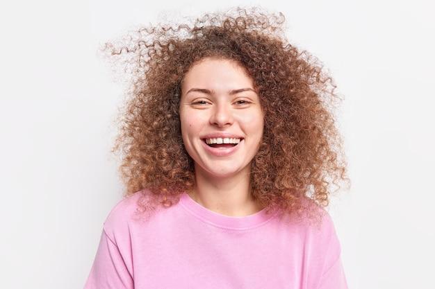 Horizontaal schot van vrolijk millennial meisje glimlacht breed toont tanden heeft krullend borstelig haar, drukt vreugde uit in een goed humeur draagt een casual roze trui geïsoleerd over een witte muur. emoties