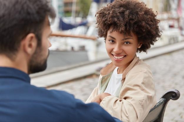 Horizontaal schot van vrolijke afro-amerikaanse meisje glimlacht breed