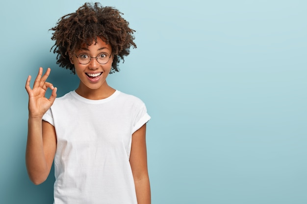 Horizontaal schot van vrolijke afro-amerikaanse vrouw maakt oke gebaar, is het eens met goed voorstel