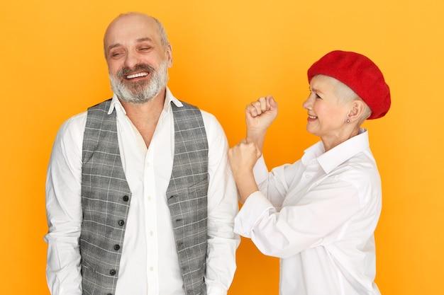 Horizontaal schot van vrolijke bebaarde kale senior man in elegante kleding glimlachend met onzorgvuldige gezichtsuitdrukking, zijn woedende woedende vrouw van middelbare leeftijd wordt boos, ponsen hem in de schouder, gekibbel