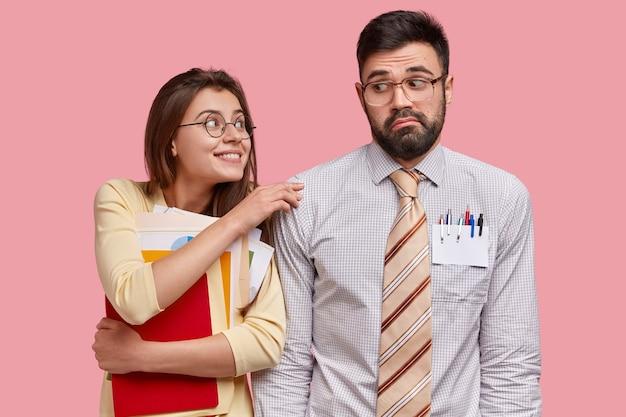 Horizontaal schot van vrolijke dame draagt papieren stelt vraag in mannelijke klasgenoot die uitdrukking in verwarring heeft gebracht