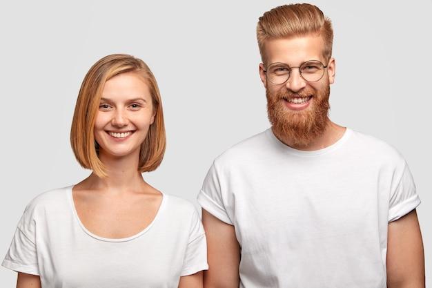 Horizontaal schot van vrolijke man en vrouw gekleed in casual witte t-shirts