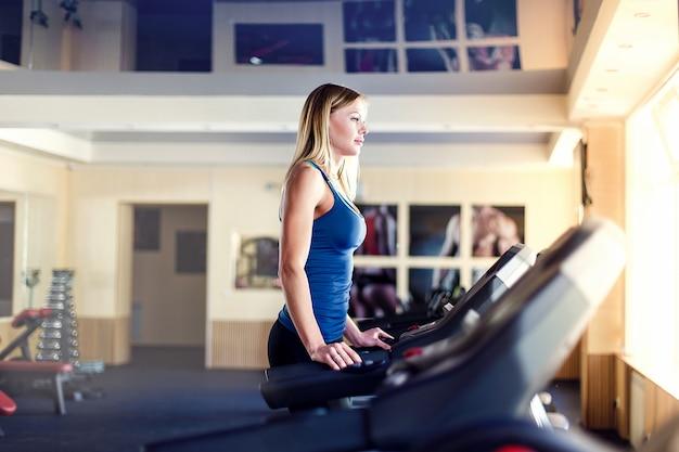 Horizontaal schot van vrouw die op tredmolen bij gezondheidsclub aanstoot. wijfje dat bij een gymnastiek uitwerkt die op een tredmolen loopt.