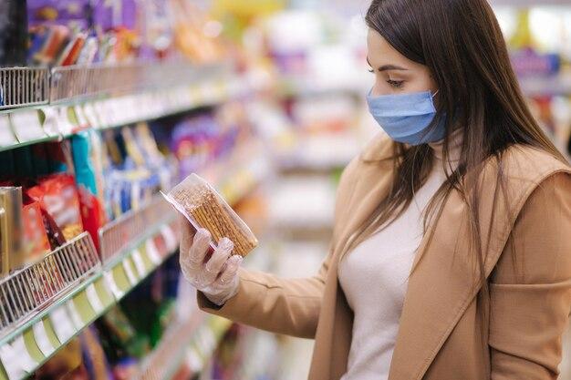 Horizontaal schot van vrouw in beschermend masker en handschoenen die etiket met prijs bij goederen lezen terwijl