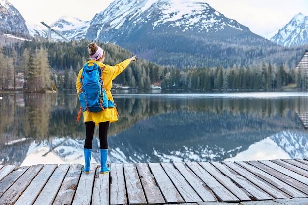 Horizontaal schot van vrouwelijke reiziger in gele regenjas en blauwe rubberlaarzen staat voor berglandschap