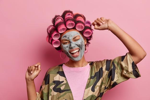 Horizontaal schot van zorgeloos blij vrouwelijk model danst met opgeheven armen knipoogt en glimlacht in grote lijnen maakt krullend kapsel gekleed in vrijetijdskleding geïsoleerd over roze muur. binnenlandse stijl