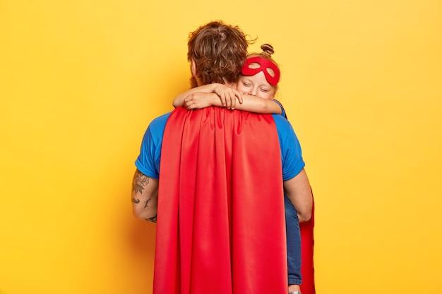Horizontaal schot van zorgzame vader draagt kleine dochter, ontvangt warme knuffel