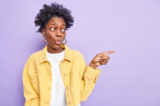 Horizontaal schot van zwarte vrouw met krullend haar heeft indruk gemaakt op geschokte gezichtsuitdrukkingspunten met wijsvinger weg