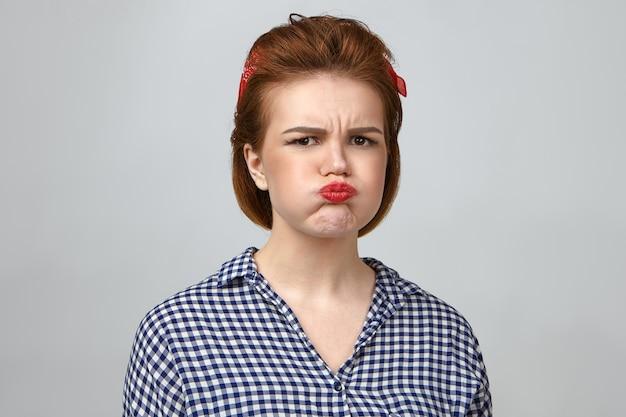 Horizontaal studioportret van geïrriteerd mooi meisje van in de twintig die ontevredenheid, wangen en pruilende lippen uitdrukt