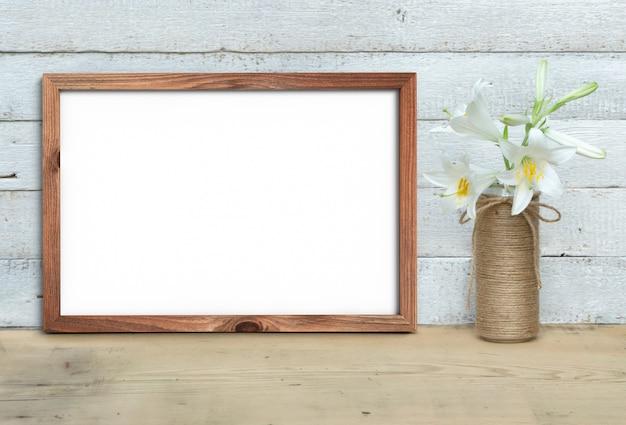 Horizontale a4 old wooden frame mockup in de buurt van een boeket van lelies staat op een houten tafel