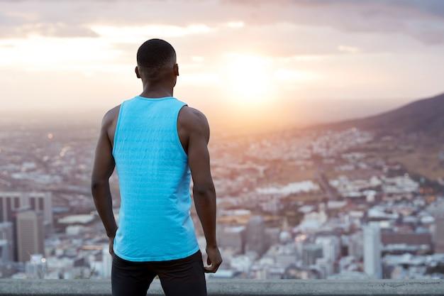 Horizontale achteraanzicht van atletische man in vrijetijdskleding, draagt een blauw vest, neemt pauze na het joggen, staat bovenop voor een prachtig uitzicht op de natuur tijdens de ochtend. mensen, vrijheid concept