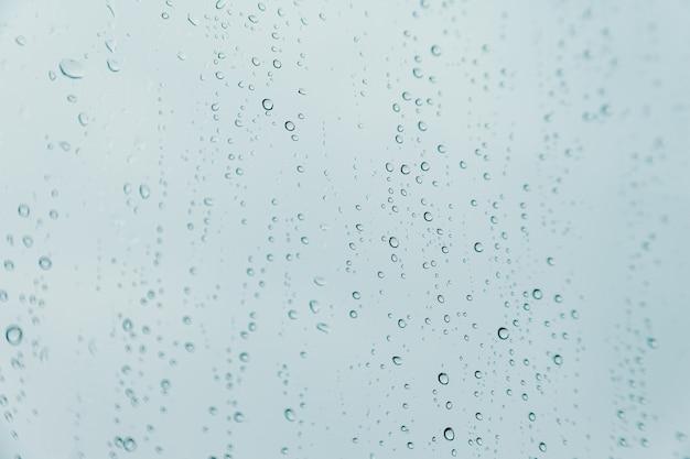 Horizontale achtergrond van enkele regendruppels over een kristaloppervlak