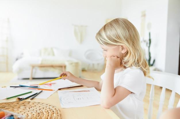 Horizontale afbeelding van creatieve getalenteerde europese kindje met losse blonde haren zit op houten bureau in stijlvolle slaapkamer interieur met vellen papier en kleurrijke potloden, lijzelen en schilderen