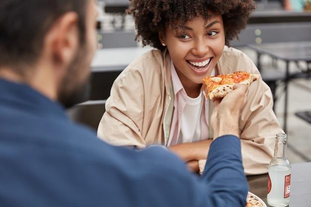 Horizontale bijgesneden weergave van vrolijke zwarte vrouw met afro kapsel eet heerlijke italiaanse pizza uit vriendjes handen