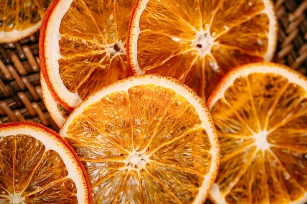 Horizontale close-up op gedroogde stukjes sinaasappel in een mandje