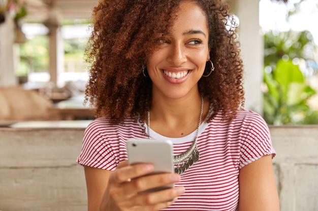 Horizontale foto van blije inhoud afro-amerikaanse dame houdt moderne mobiele telefoon vast, ontvangt een aangename melding, kijkt positief opzij, gekleed in een casual t-shirt, merkt iets geweldigs in de buurt op