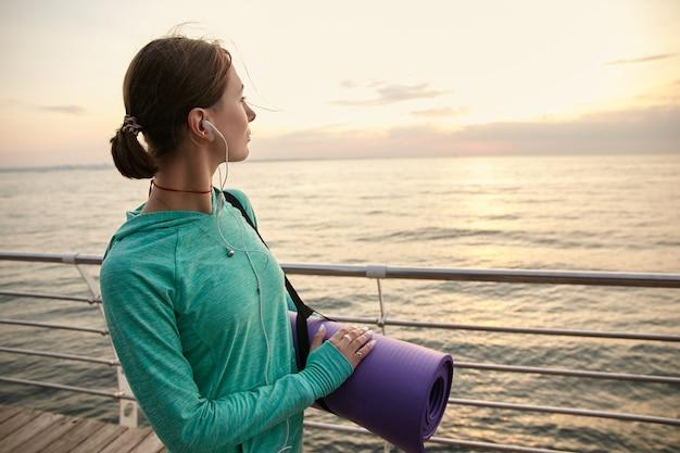Horizontale foto van een dame aan de kust in de ochtend, yoga gaan beoefenen en 's ochtends strekken, een paarse yogamat vasthouden en naar de zee kijken.