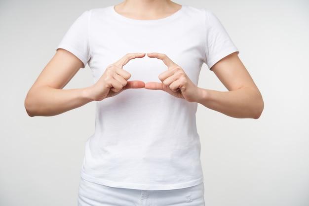 Horizontale foto van een jonge vrouw die gebarentaal leert, ellips maakt met haar vingers terwijl ze woordschool toont, geïsoleerd op witte achtergrond