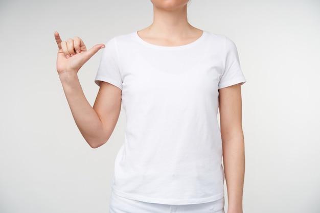 Horizontale foto van een jonge vrouw gekleed in vrijetijdskleding die de hand omhoog houdt terwijl ze de letter y op gebarentaal toont, geïsoleerd op een witte achtergrond