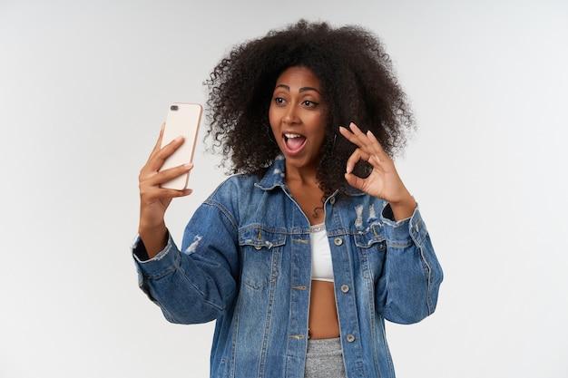 Horizontale foto van een positief gekrulde vrouw met een donkere huid die een goed gebaar toont met opgeheven hand, de mond wijd open houdt terwijl ze over een witte muur poseert, een mobiele telefoon vasthoudt en een selfie maakt