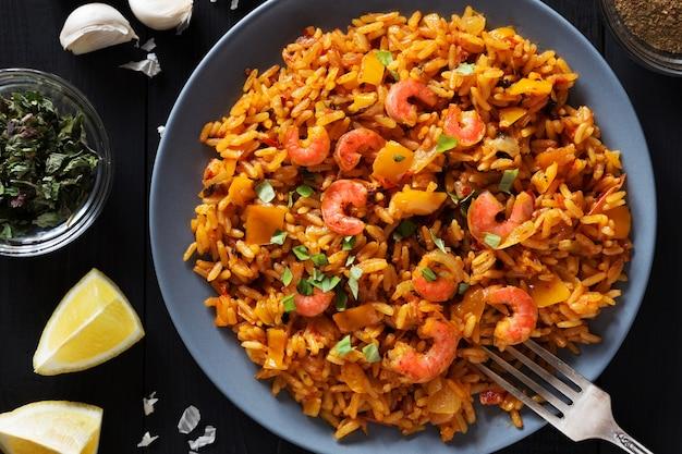 Horizontale foto van gebakken rijst met garnalen, citroen en groenten op grijze plaat overhead s