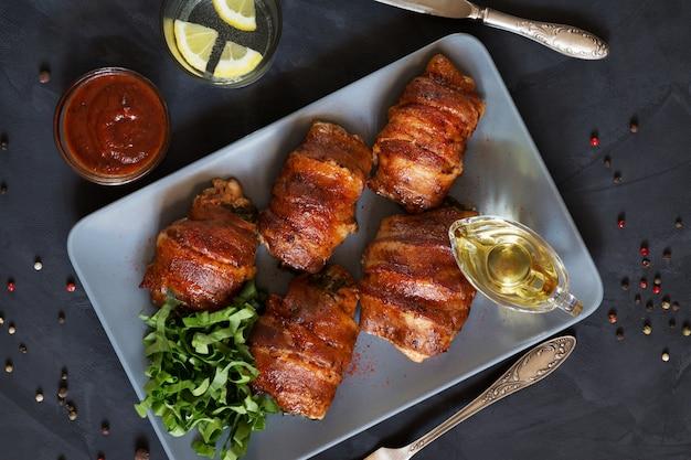 Horizontale foto van gevulde kippenborsten die in bacon op grijze dienblad hoogste mening worden gerold