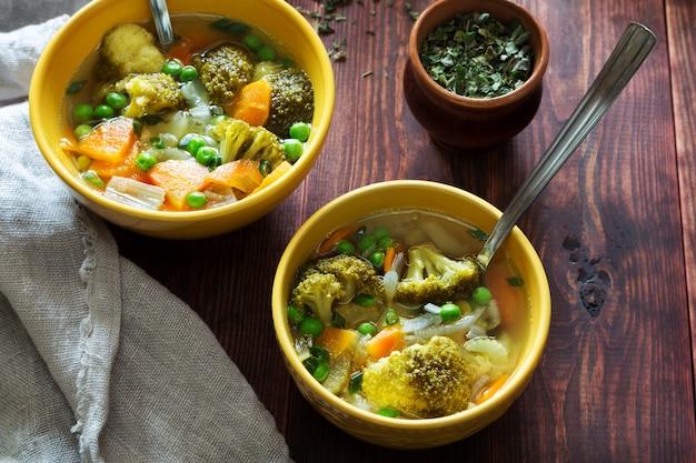 Horizontale foto van groentesoep met wortelen, groene erwten en broccoli