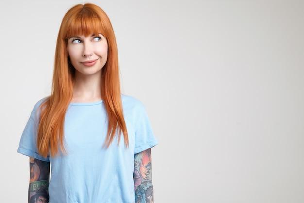 Horizontale foto van jonge langharige roodharige vrouw met tatoeages die haar gezicht grimassen terwijl ze verwonderd opzij kijkt, geïsoleerd tegen een witte achtergrond