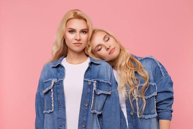 Horizontale foto van jonge mooie langharige blonde zusters met krullen dragen jeans, jassen en witte t-shirts terwijl staande op roze achtergrond met handen naar beneden