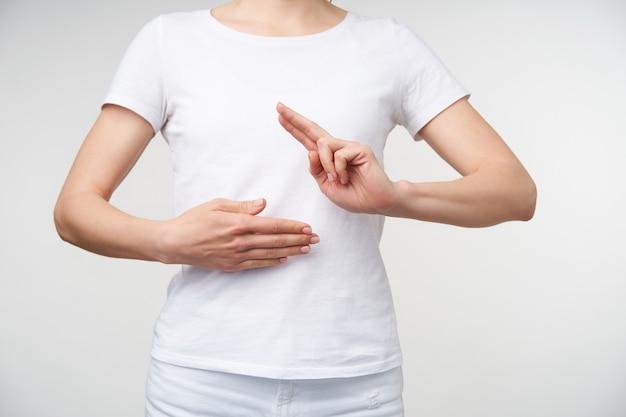 Horizontale foto van jonge vrouw die handpalm op haar buik houdt een ander omhoog terwijl het tonen van woordleraar op gebarentaal, over witte achtergrond wordt geïsoleerd