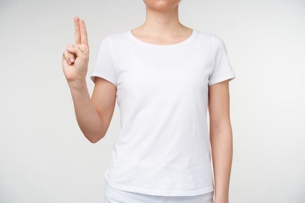 Horizontale foto van jonge vrouw die twee vingers bij elkaar houdt terwijl ze letter u toont met behulp van het alfabet van de dood, geïsoleerd op een witte achtergrond in vrijetijdskleding