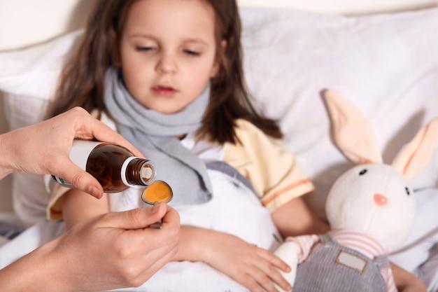 Horizontale foto van onbekende hand gietende vloeistof in lepel van flesje met stroop, persoon die om kind geeft dat in bed met griep ligt