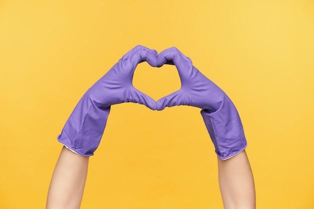 Horizontale foto van opgeheven handen gekleed in rubberen handschoenen met liefde teken, hart vormen met vingers terwijl wordt geïsoleerd op gele achtergrond