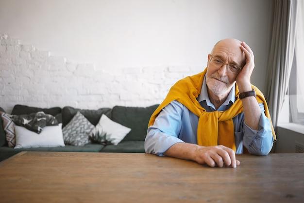 Horizontale foto van stijlvolle volwassen zestigjarige advocaat zittend op zijn werkplek in modern kantoor interieur, met een kleine pauze, hoofd bij de hand rustend, trui om zijn nek dragen, moe kijken