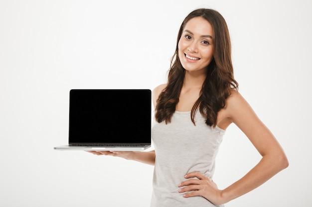 Horizontale foto van tevreden opgeleide vrouw die en het zwarte lege scherm van zilveren laptop glimlacht aantoont die over witte muur houdt