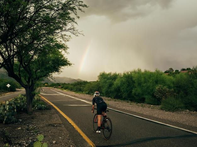 Horizontale foto van vrouwelijke fietser in beweging die een fiets op de weg over de natuur rijdt