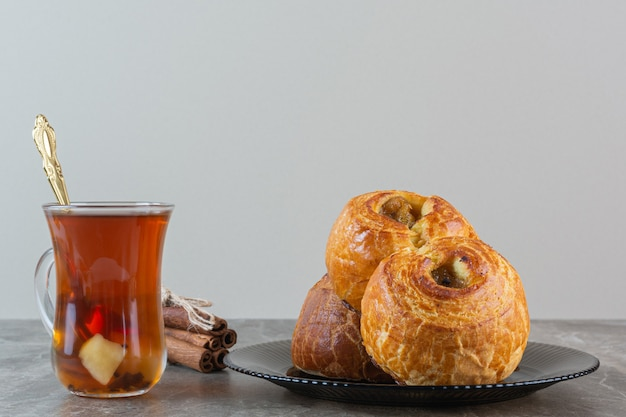 Horizontale foto van zelfgemaakte koekjes met thee op grijs.