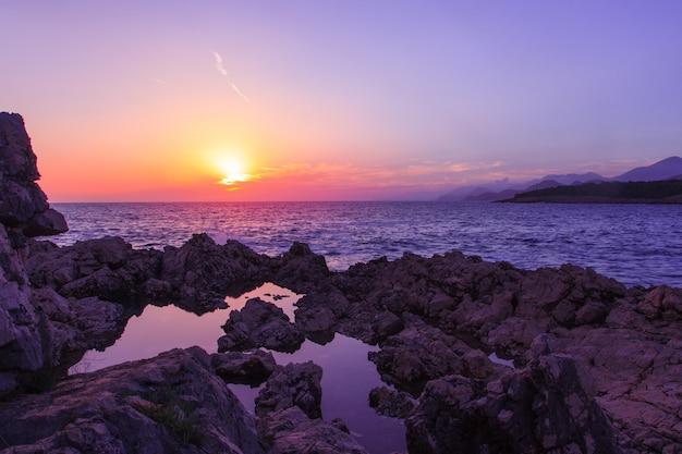 Horizontale foto van zonsondergang op het rotsachtige strand