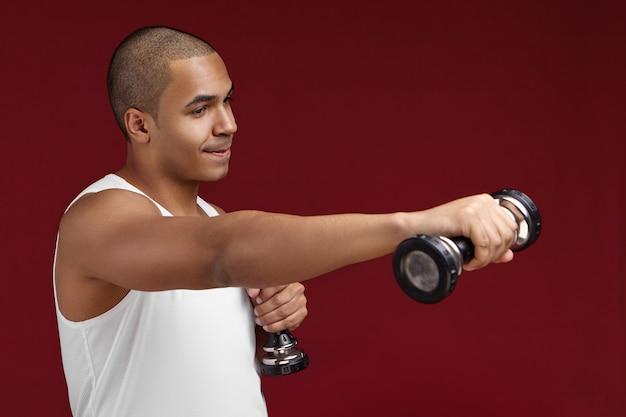 Horizontale geïsoleerde shot van aantrekkelijke gespierde jonge afrikaanse man met goed gedefinieerde biceps gewichtheffen in de studio. knappe donkere bodybuilder trainen in de sportschool, met behulp van twee halters