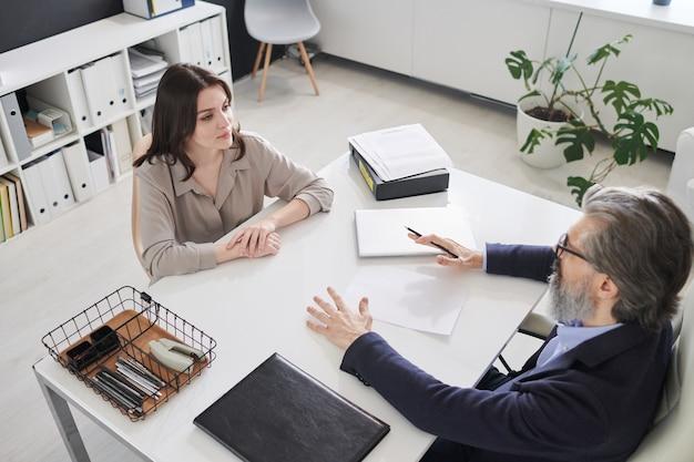 Horizontale hoge hoekmening van aantrekkelijke jonge vrouw die voor een volwassen man aan het bureau zit met een sollicitatiegesprek