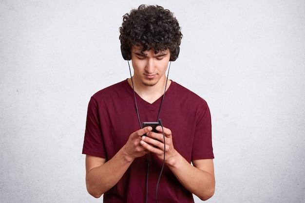 Horizontale jonge man messaging en bloggen op mobiel terwijl het luisteren van muziek in de oortelefoon. knappe man poseren op muur met lege kopie ruimte. mensen en technologie concept.