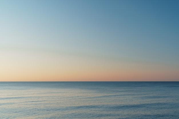 Horizontale lijn tussen zee en lucht bij zonsondergang. statische minimalistische compositie