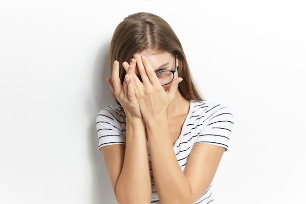 Horizontale mooie jonge vrouw die een bril draagt die gluurt, het gezicht bedekt met beide handen, door de vingers kijkt met een verlegen, verlegen of bange gezichtsuitdrukking