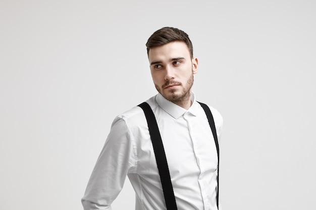 Horizontale opname van aantrekkelijke jonge bebaarde blanke werknemer gekleed in een elegant pak poseren in studio, opzij kijken met ernstige peinzende uitdrukking, nadenken over zakelijke ideeën en plannen
