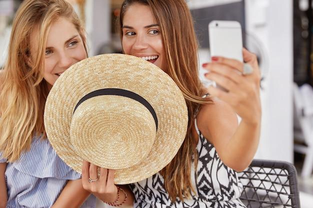 Horizontale opname van aantrekkelijke mooie vrouwen verstoppen zich achter strooien hoed, selfie maken met telefoon, hun foto's online op sociale netwerken delen. opgetogen lesbisch stel maakt een foto van zichzelf