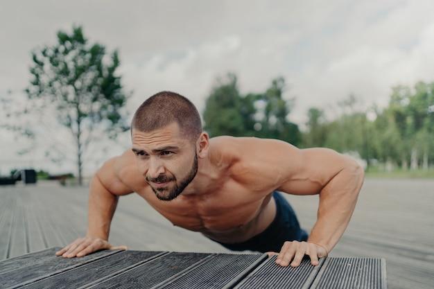 Horizontale opname van actieve bebaarde europese man doet oefeningen voor de shouldrs, borst en biceps, blijft in goede fysieke vorm, vormt buiten, heeft gespierde armen.