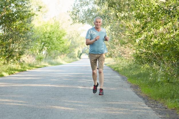 Horizontale opname van actieve senior man loopt zeer snel op asfalt, gekleed in slijtage, gaat regelmatig sporten, ademt frisse lucht in op het platteland. rijpe hardloper heeft een gezonde levensstijl.